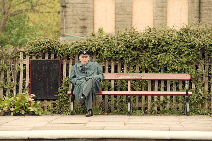 Uniformed man sat on a bench at Ramsdown (Ramsbottom) Steam Railway Station, part of the East Lancashire Railway